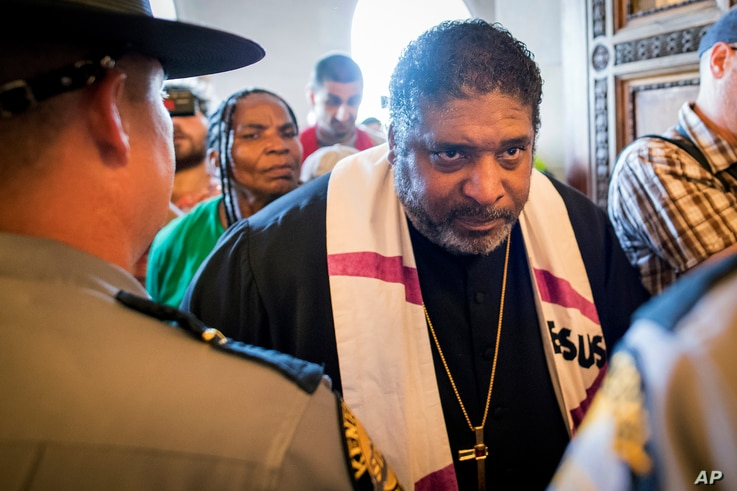 FILE - The Reverend William J. Barber argues with state troopers at the doors of the Capitol during a protest organized by the Kentucky Poor People's Campaign in Frankfort, Ky., June 4, 2018. Anti-poverty activists were denied group access to the Cap...