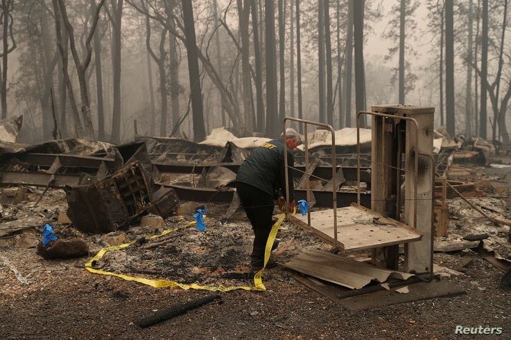 A Butte County Sheriff deputy places yellow tape at the scene where human remains were found during the Camp fire in Paradise, California, Nov. 10, 2018.
