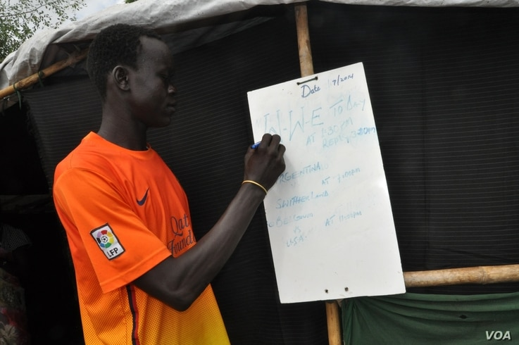 David Rajor Konyi writes the day's program on a whiteboard outside the makeshift cinema that he set up and runs in an  UNMISS camp for the displaced in the South Sudanese capital, Juba.