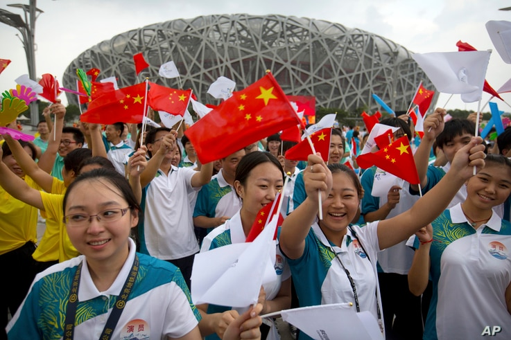 Participants wave flags and cheer before the announcement that Beijing will host the 2022 Winter Olympics at a gathering outside the Beijing Olympic Stadium, also known as the Birds Nest, in Beijing, July 31, 2015.
