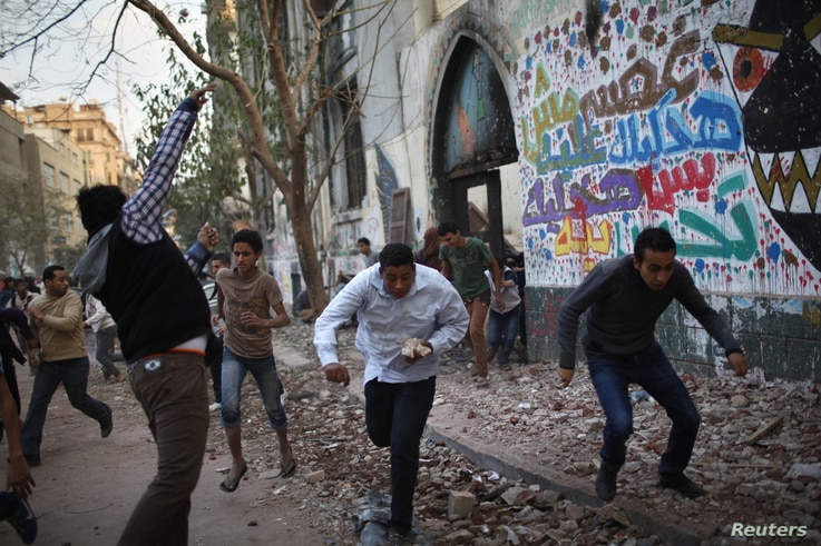 A protester throws stones as others run for cover during clashes with riot police at Tahrir Square in Cairo, November 26, 2012.