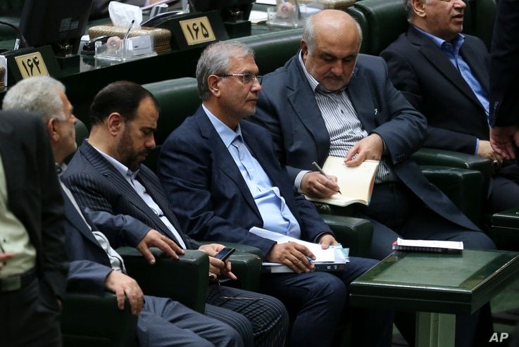 Iran's Labor Minister Ali Rabiei, center left, listens to a speaker during his impeachment hearing in an open session of parliament, in Tehran, Aug. 8, 2018.