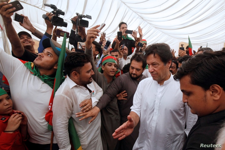 FILE - Imran Khan (2nd R), chairman of the Pakistan Tehreek-e-Insaf (PTI) political party, gestures as he walks among supporters during a campaign rally ahead of general elections in Karachi, Pakistan, July 4, 2018.