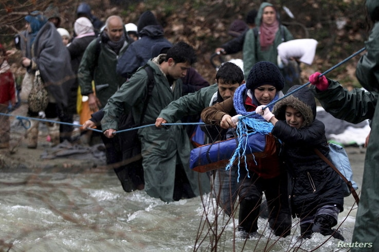 Refugees and migrants attempt to cross a river near the Greek-Macedonian border to enter Macedonia after an unsuccessful attempt yesterday, west of the village of Idomeni, Greece, March 15, 2016