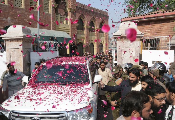 Supporters of Hafiz Saeed, head of Pakistan's Jamaat-ud-Dawa group, shower his car with rose petals as he leaves a court in Lahore, Pakistan, Nov. 21, 2017.