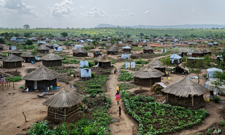 FILE - Women and children return home with containers of water, in a section of the Bidi Bidi refugee settlement in northern Uganda, June  9, 2017. The number of South Sudanese refugees sheltering in Uganda has reached 1 million, the United Nations s...