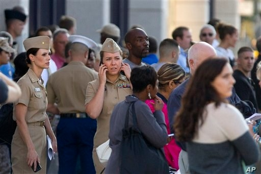 Family and friends wait to greet staff of the Navy Yard as they are bused to Nationals Park, in Washington, Sept. 16, 2013.