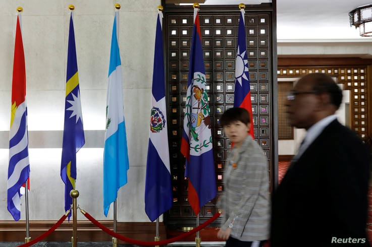 People walk next to the flag of the Dominican Republic (3rd R) inside the Taiwan Ministry of Foreign Affairs in Taipei, Taiwan, May 1, 2018.