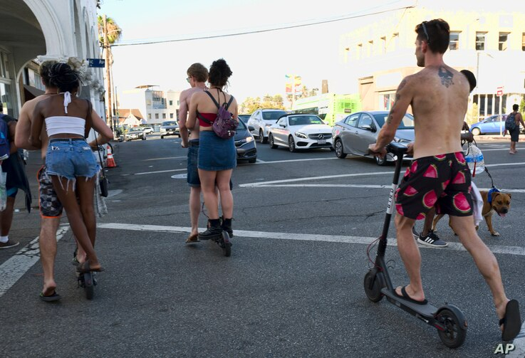 FILE - In this July 24, 2018, file photo, riders make their way across a street on Bird electric scooters in the Venice Beach section of Los Angeles.
