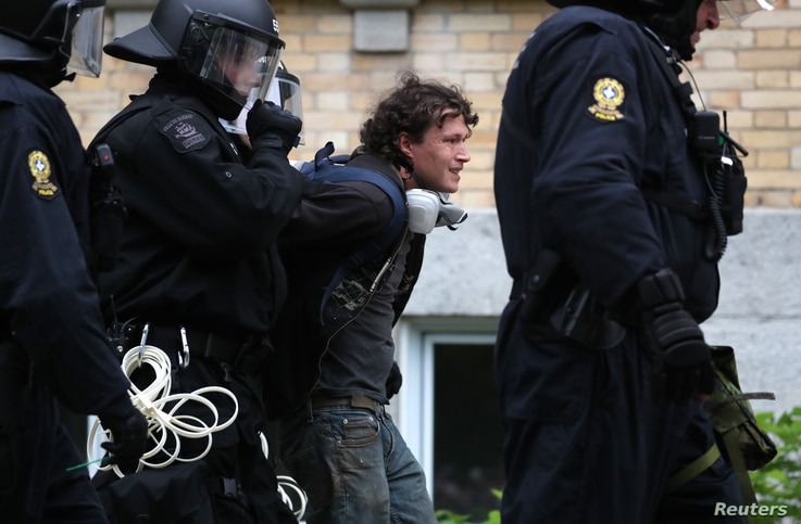 Riot police arrest a protester at a march by demonstrators during the G-7 Summit in Quebec City, Quebec, Canada, June 7, 2018.