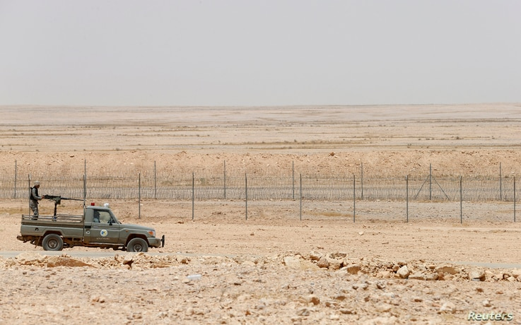 FILE - A military truck belonging to the Saudi border guards force patrol near a fence on Saudi Arabia's northern borderline with Iraq.