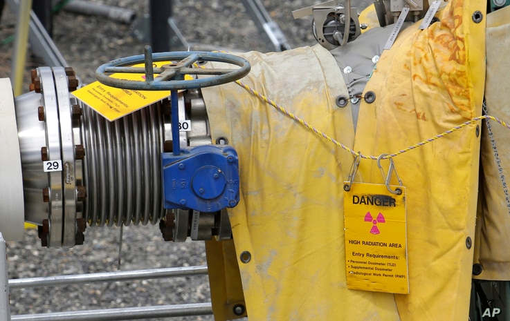 """In this July 9, 2014 file photo, a sign warns of high levels of radiation near a valve at the """"C"""" tank farm during a media tour of the Hanford Nuclear Reservation near Richland, Washington."""