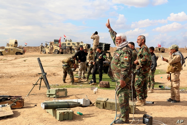 Iraqi army soldiers and volunteers prepare to launch mortar shells and rockets against Islamic State militant positions outside Tikrit, March 4, 2015.