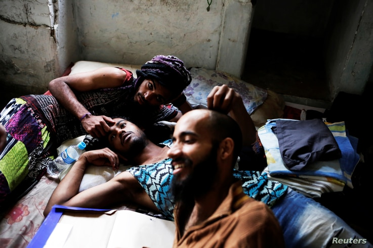 Rodrigo (right), 26, Wam (center), 24, and Teflon, 19, members of the lesbian, gay, bisexual and transgender (LGBT) community who have been invited to live in a building, relax in downtown Sao Paulo, Brazil, Nov. 8, 2016.