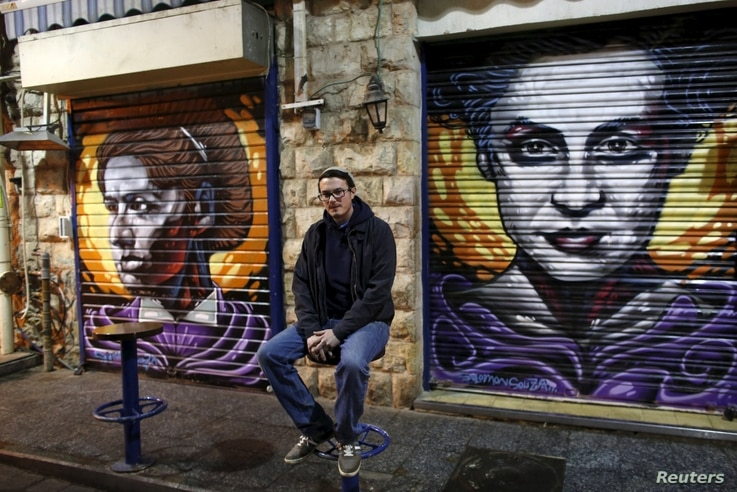 Artist Solomon Souza poses for a picture near portraits he spray-painted on metal shutters of closed storefronts in Mahane Yehuda, one of Jerusalem's most popular outdoor markets, Feb. 24, 2016.