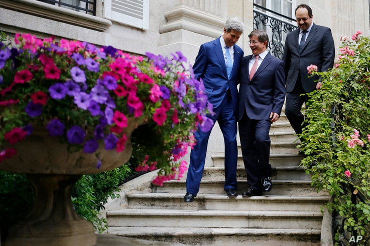 U.S. Secretary of State John Kerry, Qatari Foreign Minister Khaled al-Attiyah, right, and Turkish Foreign Minister Ahmet Davutoglu walk down a staircase at the Turkish ambassador's residence in Paris, 26 July, 2014.