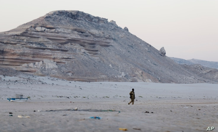 FILE - In this photo taken March 6, 2017, a Somali government soldier walks on the beach in Eyl, in Somalia's semiautonomous northeastern state of Puntland. Somali pirates have seized a small boat, kidnapped its Indian crew members, and are taking th