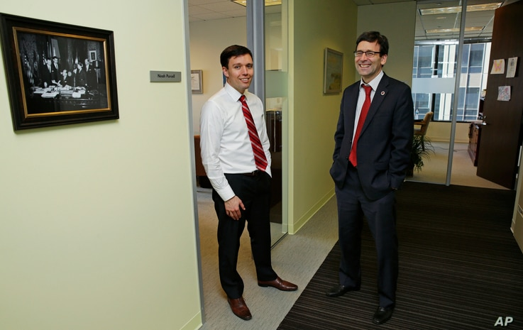 Washington state Solicitor General Noah Purcell (left) and Attorney General Bob Ferguson pose for a photo next to their adjoining offices in Seattle.
