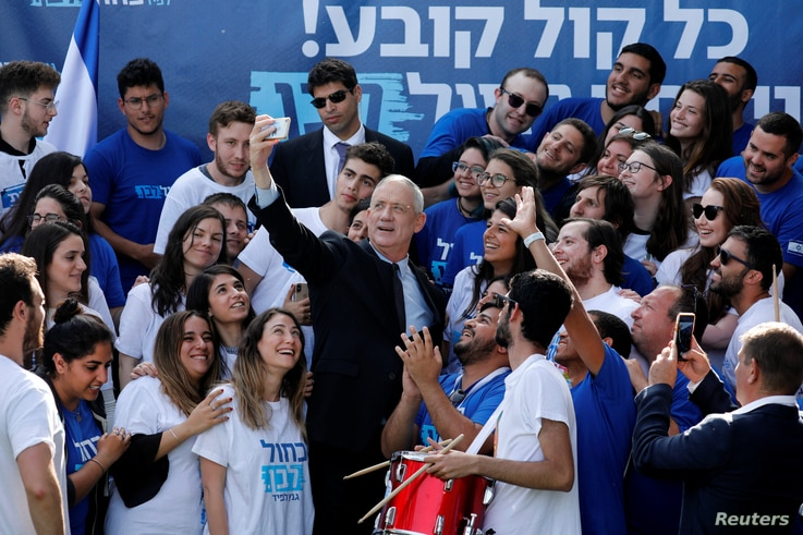 Benny Gantz, leader of Blue and White party, takes a selfie with supporters outside the party headquarters in Tel Aviv, Israel, April 8, 2019.