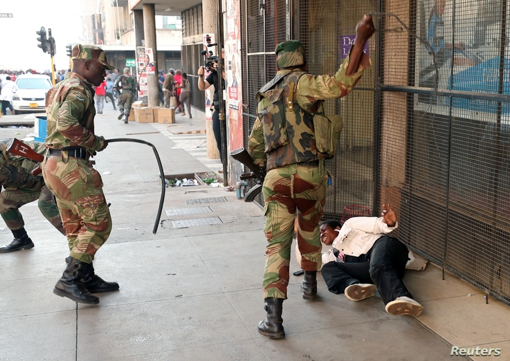 Soldiers beat a supporter of the opposition Movement for Democratic Change party of Nelson Chamisa outside the party's headquarters as they await the results of the general elections in Harare, Zimbabwe, Aug. 1, 2018.