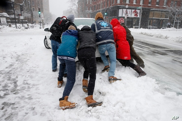 People push a stranded taxi during a snowstorm in Boston, March 13, 2018.