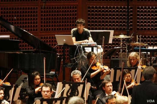 Mason Bates 'plays' the computer with the San Francisco Symphony for the world premiere of his symphony, The B-Sides, May 2009.