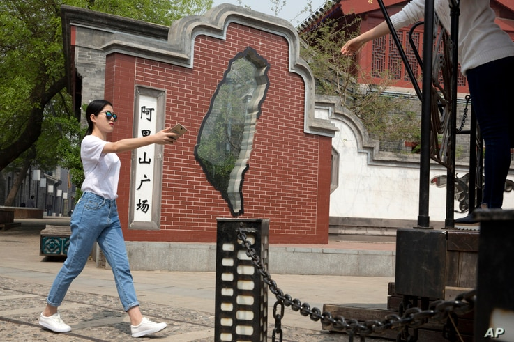 Tourists prepare to take photos in a retails area with a Taiwan theme showing a map of Taiwan in Beijing, China,  April 13, 2016. The deportation of nearly four dozen Taiwanese from Kenya to China where they are being investigated over wire fraud all...
