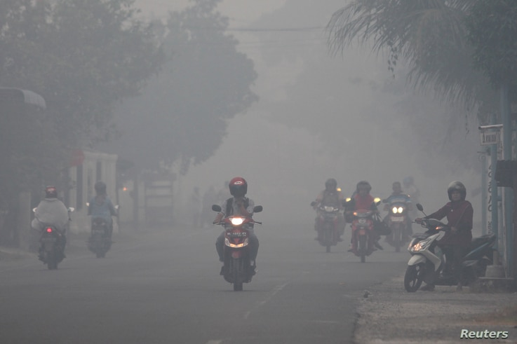 FILE - A resident drives a motorcycle through a haze produced by peatland fires at Suak Raya village in Aceh Barat, Aceh province, Indonesia, July 27, 2017 in this photo taken by Antara Foto.