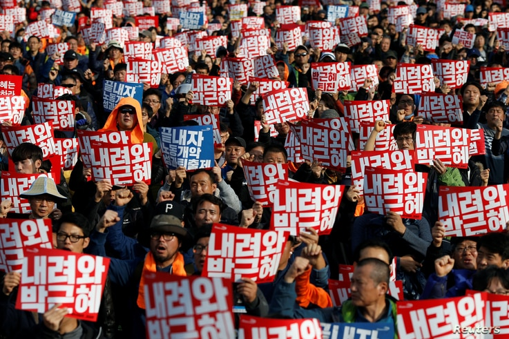 """People chant slogans at a rally calling for President Park Geun-hye to step down in central Seoul, South Korea, Nov. 12, 2016. The placards read, """"Step down Park Geun-hye."""""""