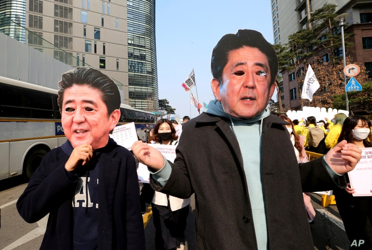College students wearing masks of Japanese Prime Minister Shinzo Abe march toward Japanese embassy during a rally to mark the centennial of the March First Independence Movement Day against Japanese colonial rule (1910-45), in Seoul, South Korea, Mar...