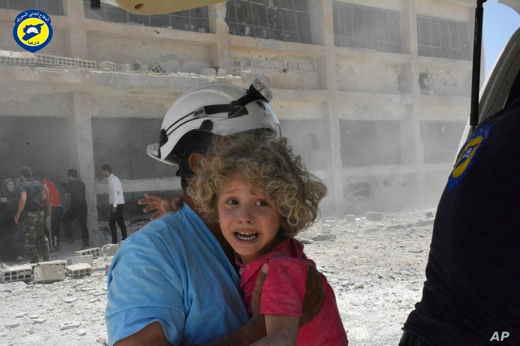 This photo provided by the Syrian Civil Defense, shows a White Helmets worker carrying a child after airstrikes hit a school housing a number of displaced people in the  Daraa province of Syria,  June 14, 2017.