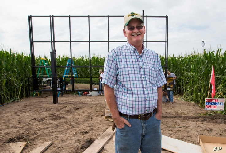 In this July 29, 2017 photo, corn farmer Jim Carlson of Silver Creek, Ne., waits to be interviewed by a television reporter while standing in front of solar panels he is building on his land in the proposed path of the Keystone XL pipeline.