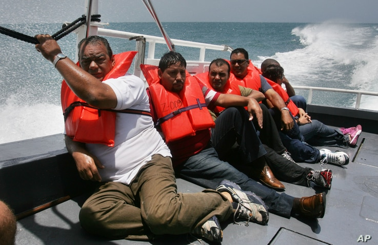FILE - En route to a processing center on mainland Puerto Rico about three hours away, Cuban migrants picked up earlier on Puerto Rico's remote Mona Island sit on the deck of a U.S. Border Patrol boat.