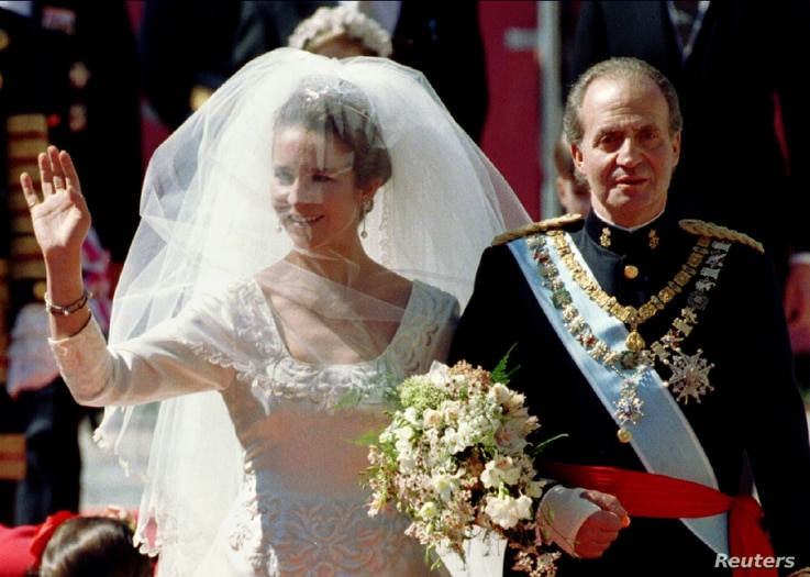 Spain's Princess Elena waves to the crowds as she is escorted by her father King Juan Carlos to the altar of Seville's cathedral on March 18, 1995.