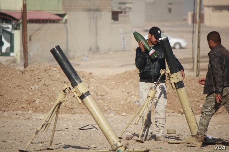 An Iraqi soldier loads a mortar to fire into IS-held areas on the outskirts of Mosul, Iraq, Nov. 23, 2016. (H. Murdock/VOA)