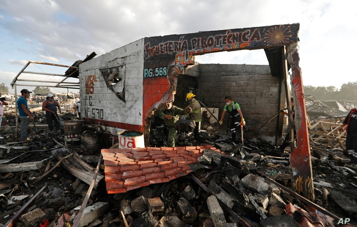 Firefighters and rescue workers remove debris from the scorched ground of Mexico's best-known fireworks market after an explosion explosion ripped through it, in Tultepec, on the outskirts of Mexico City, Mexico, Dec. 20, 2016.