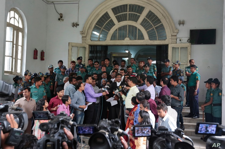 Prosecutor, Sultan Mahmud Simon, center, wearing black coat, talks to the media in front of a special war crimes court after the court sentenced four men to death in Dhaka, Bangladesh, Tuesday, May 3, 2016.