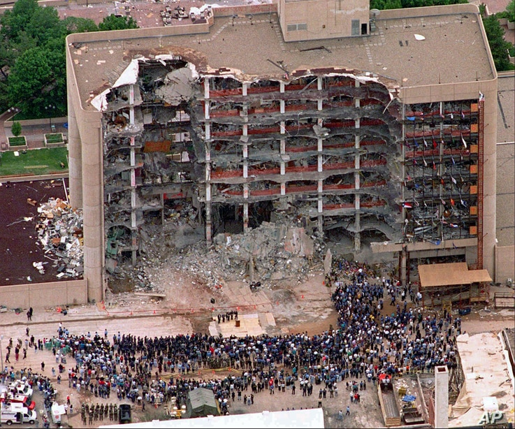 FILE - In this May 5, 1995, photo, search and rescue personnel attend a memorial service in front of the Alfred P. Murrah Federal Building in Oklahoma, destroyed by a fertilizer bomb in what is considered the first major domestic terrorist attack in ...