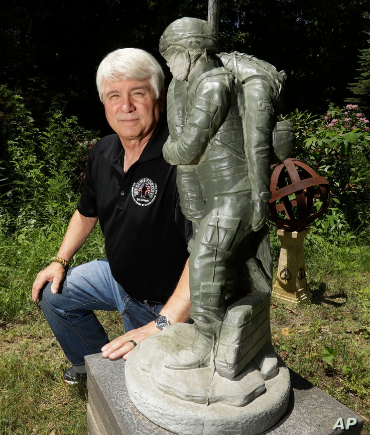 In a photo from June 9, 2017, former Army medic James McCloughan kneels next to a statue presented to him by a fellow soldier in South Haven, Michigan. McCloughan saved the lives of 10 soldiers during the Battle of Nui Yon Hill in May 1969 in Vietnam...