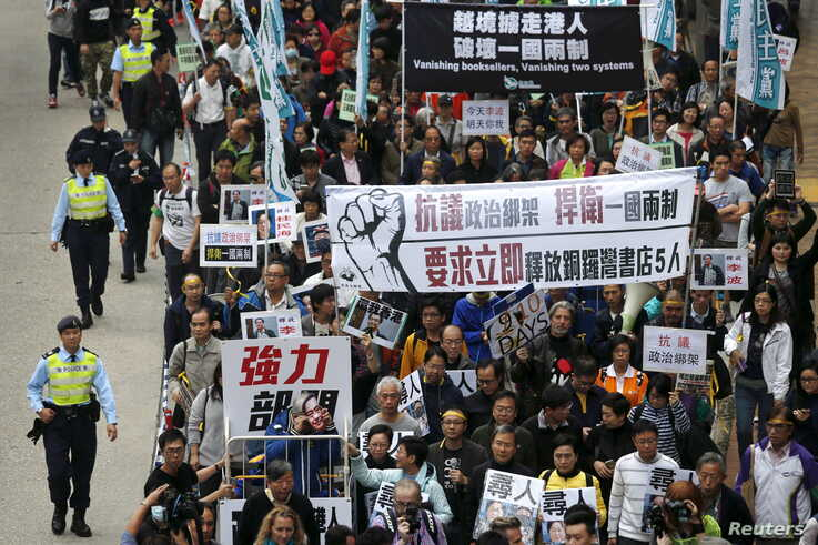 "Demonstrators march during a protest over the disappearance of booksellers in Hong Kong, Jan. 10, 2016. The banner reads, ""Against political kidnapping. Safeguarding One Country, Two Systems. Demanding the immediate release of the five people from Ca"