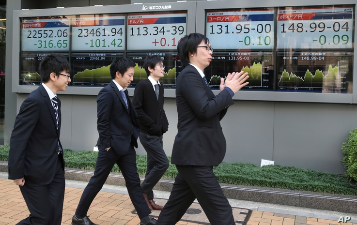 People walk by the electronic stock boards of a securities firm in Tokyo, Nov. 10, 2017. Asian shares sank Friday, following declines on Wall Street after a proposed delay to U.S. tax cut plan dented investor sentiment.