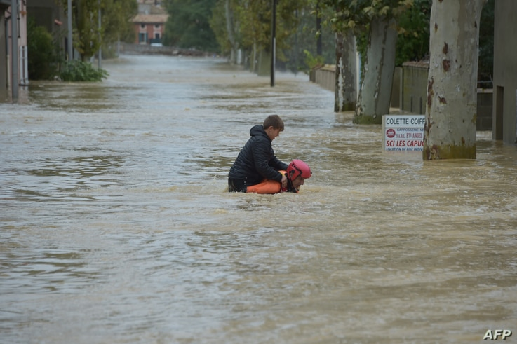 A firefighter helps a youngster to evacuate in a flooded street during a rescue operation following heavy rains that saw rivers bursting banks on Oct. 15, 2018 in Trebes, near Carcassone, southern France.