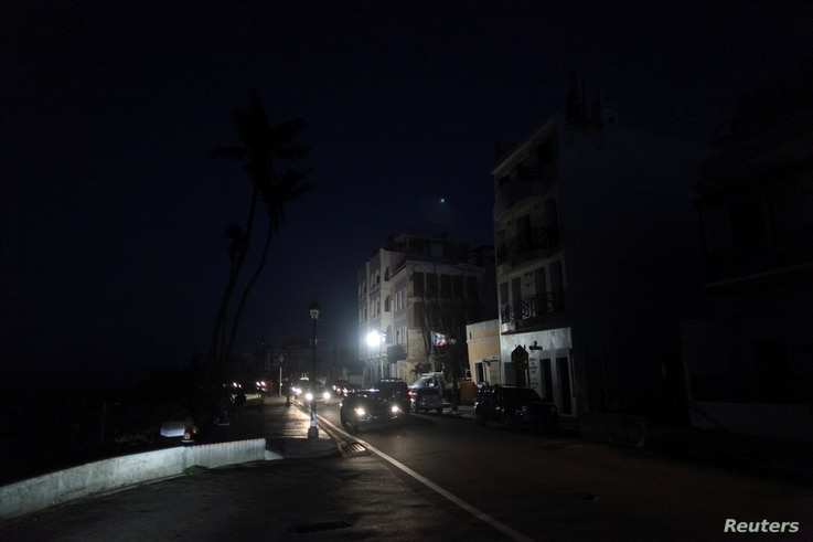 Cars drive on a street in the light of a generator-powered lamp set up by the municipality, after Hurricane Maria hit the island and damaged the power grid in September, in Old San Juan, Puerto Rico Oct. 26, 2017.