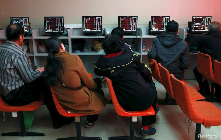 FILE - Investors look at computer screens showing stock information at a brokerage house in Shenyang, Liaoning province, April 13, 2015.