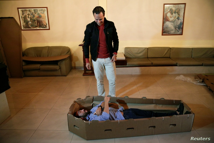 Elio Angulo (bottom C) lies inside a cardboard coffin next to Alejandro Blanchard as they introduce their product to potential customers at a mortuary in Valencia, in the state of Carabobo, Venezuela, Aug. 25, 2016.