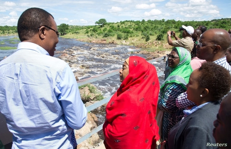 Tanzanian Vice President Samia Suluhu Hassan (in red shawl) is briefed about the destruction of the Ruaha River, in Kilolo district, Tanzania, May 8 2017.