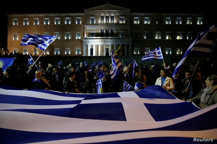 Protesters hold a giant Greek national flag during a demonstration against the agreement reached by Greece and Macedonia to resolve a dispute over the former Yugoslav republic's name, in front of the parliament building in Athens, Greece, Jan. 24, 20...