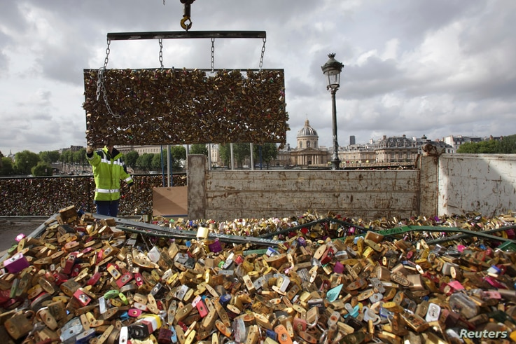 """City municipal employees lower iron grills covered with """"love locks"""" into a truck after they were  removed from the Pont des Arts in Paris, France, June 1, 2015. The bridge is closed from June 1 to June 8 and the padlocks which hang on the bridge wil..."""