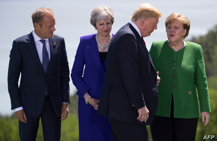 European Council President Donald Tusk,from left, British Prime Minister Theresa May and German Chancellor Angela Merkel look on as US President Donald Trump arrives for the group photo  at the G7 Summit, June 8, 2018.
