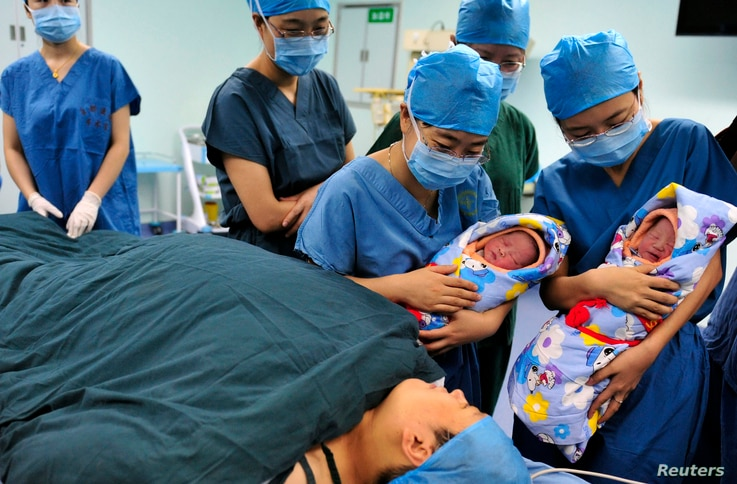 FILE - Nurses show a pair of fraternal twins to their mother (bottom) after they were born at the IVF centre of a hospital in Xi'an, Shaanxi province.